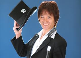 関西(大阪)のマジシャン大道芸人MIKIYAがシルクハットを持って笑顔になっている。