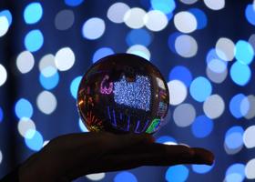 名古屋港シートレインランドにて夜にイルミネーションが輝く中で、関西(大阪)のマジシャン大道芸人MIKIYAが水晶玉を持っている様子。水晶玉に映り込む景色が美しい。