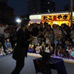 名古屋市北区の柳原商店街のお祭り(夏祭り)にて大阪の大道芸人MIKIYAがストリートパフォーマンスを行っている。数百人の観客に囲まれてマジックをしている。銀色のバケツ(ワインペール)を持ってまさにマイザーズドリームを始めようとしているところ。