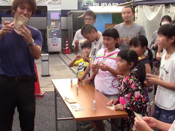 関西(大阪)のマジシャン大道芸人MIKIYAによるレクチャー(マジック教室、ワークショップ)。スバルショップ山城にてお札とトランプを使ったマジックを教えている様子。大人も子供も年齢問わず参加。