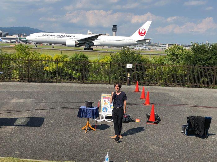 伊丹スカイパークにて。JALの飛行機が着陸する瞬間。マジシャン(大道芸人)MIKIYAがこれからマジックショーを始めるところ。