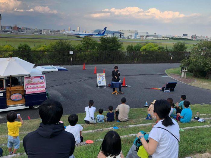 伊丹スカイパークにてマジシャン(大道芸人)MIKIYAがマジックショーを行っている。ソーシャルディスタンスを保ってのイベント開催。後ろにはANAの飛行機がある。