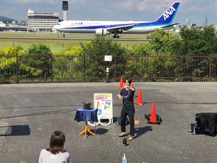 伊丹スカイパークにてANAの飛行機が着陸するタイミング。マジシャン(大道芸人)MIKIYAがチャイナリングでマジックをしている。